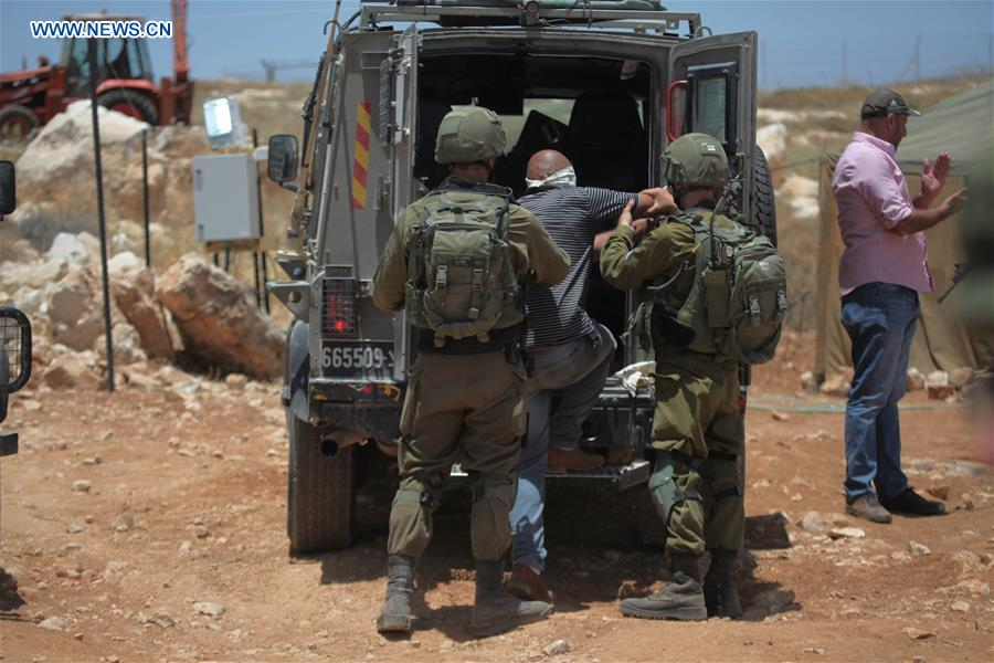 Israeli soldiers detain Palestinians during protest against new Jewish settlement outpost near Hebron