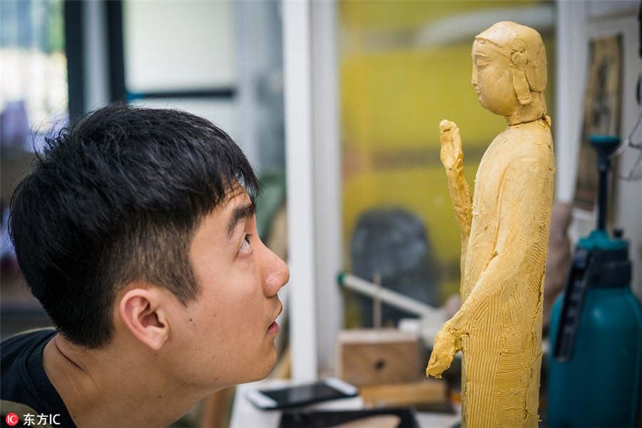 Young man devoutly makes Buddha statues