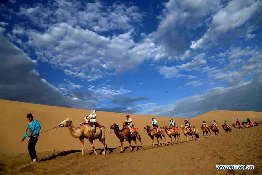 Tourists visit Mingsha Mountain and Crescent Spring scenic spot in Dunhuang, NW China