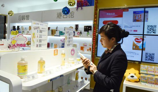 A customer selects imported items at a cross-border e-commerce experience store in Hangzhou. (Photo by Long Wei / for China Daily)