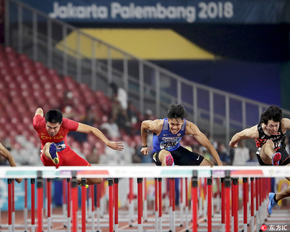 China's Xie Wenjun (L) is on his way to win the gold medal in the men's 110m Hurdles final of the Athletics events at the Asian Games 2018 in Jakarta, Indonesia, 28 August 2018. Xie Wenjun won ahead of second placed Chen Kuei-ru (C) of Taiwan and third placed Shunya Takayama (R) of Japan. [Photo: MAST IRHAM/ IC]