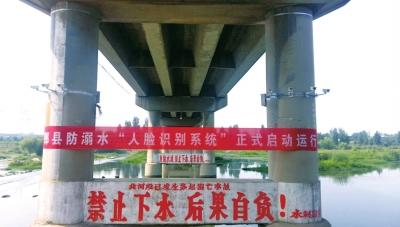 """This undated picture from Pingdingshan City in Henan Province shows the facial recognition cameras installed on bridge beside a banner that says """"A warning system to stop people from drowning based on facial recognition has been installed.""""  [File photo:dahe.cn]"""