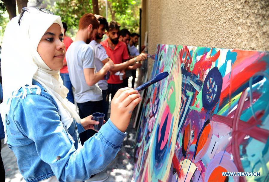 People draw paintings on sidewalk in Damascus, Syria