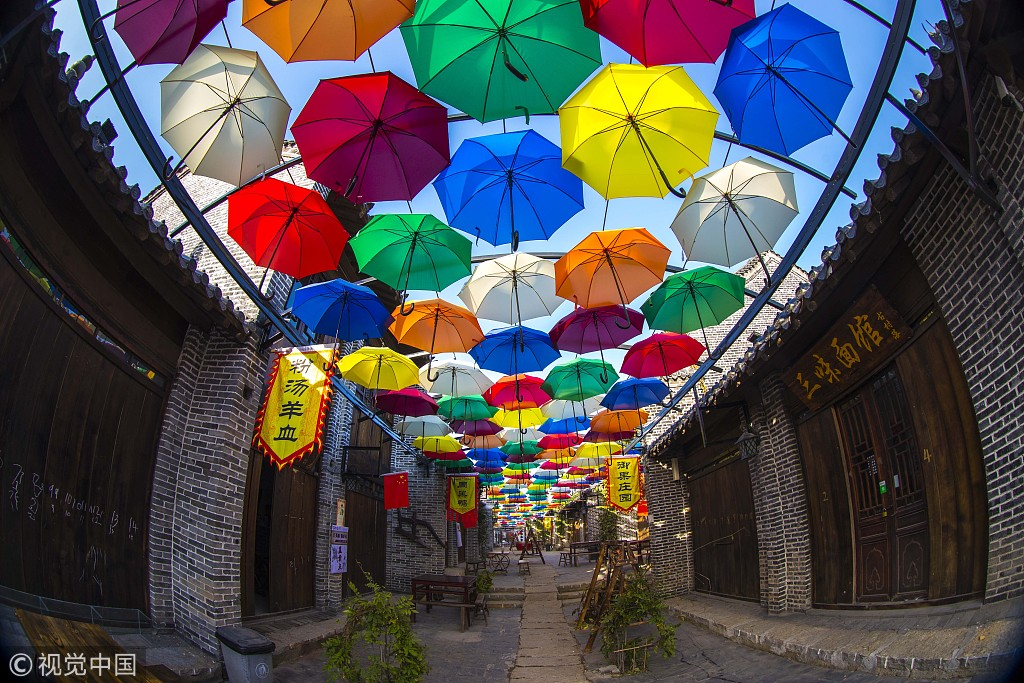 A sea of umbrellas decorate an ancient street in east China