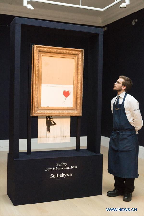 """Sotheby's staff members present Banksy's """"Love is in the Bin"""" in London"""