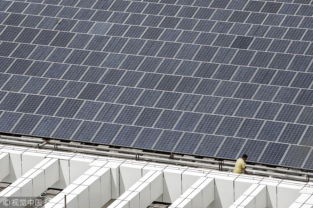 A worker walks past a rooftop solar farm at the BYD Co. headquarters in Shenzhen, China, September 21, 2017.[Photo:VCG]