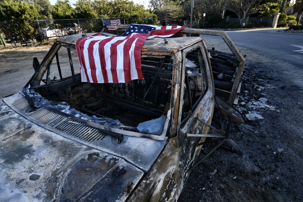 An American flag is draped over the charred remains of an old pickup truck entering Point Dume along the pacific coast highway in Malibu, Calif., on Sunday Nov. 11, 2018. [Photo: AP/Richard Vogel]