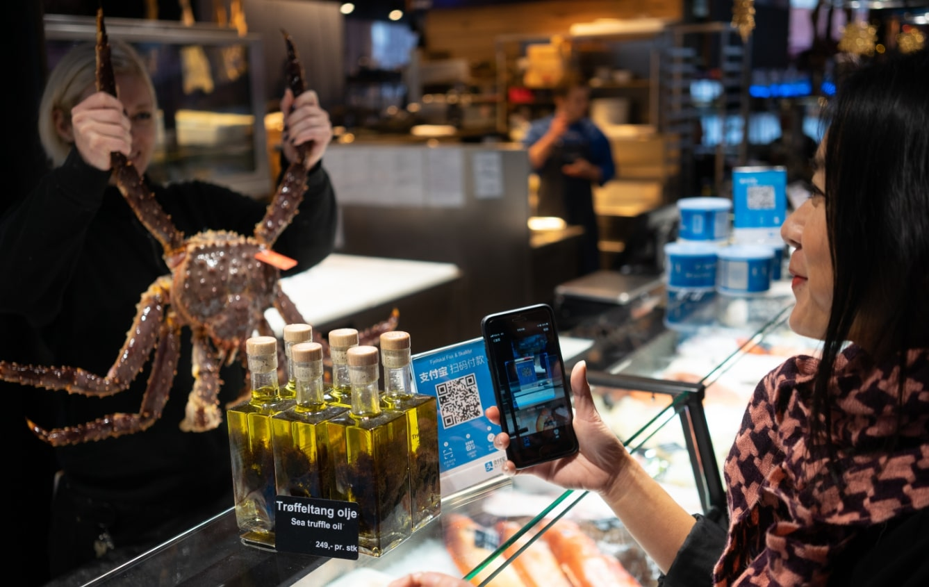 A tourist uses Alipay to pay at Fjellskal, Norway's most famous fish market. [Photo provided to China Plus]