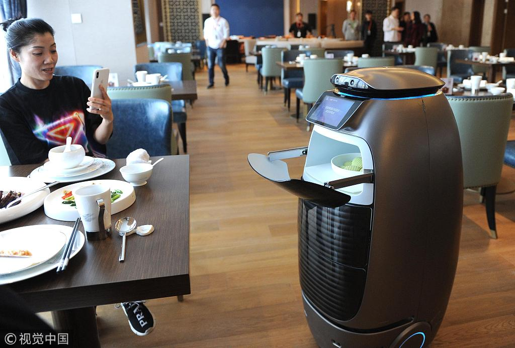 """A guest takes a picture of a food delivery robot in the restaurant at Alibaba's AI-driven """"Flyzoo Hotel"""" in Hangzhou, Zhejiang Province, December 17, 2018. [Photo: VCG]"""