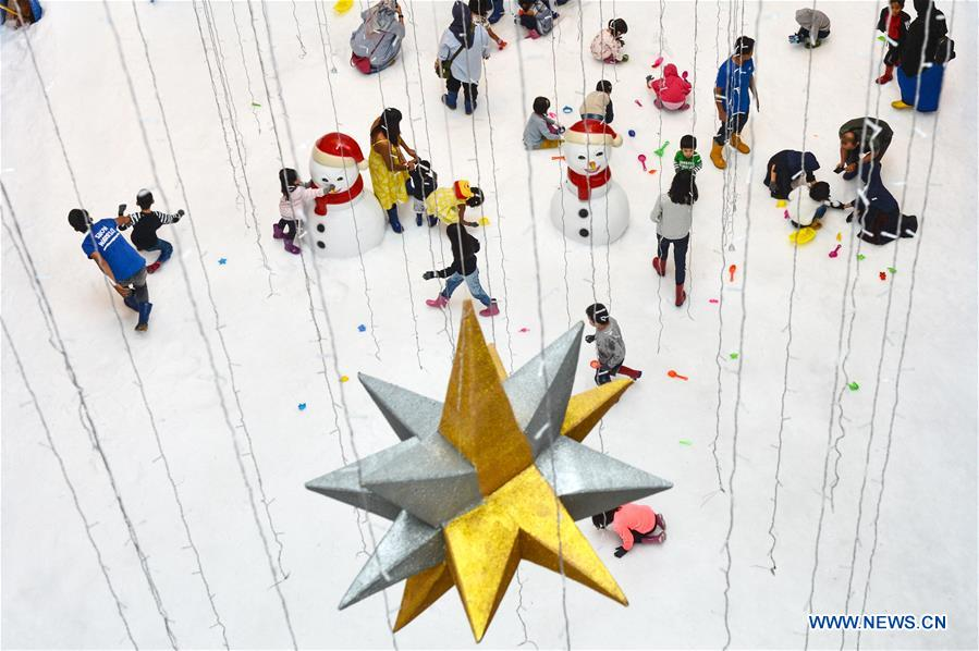 Children play in artificial snow park in Indonesia
