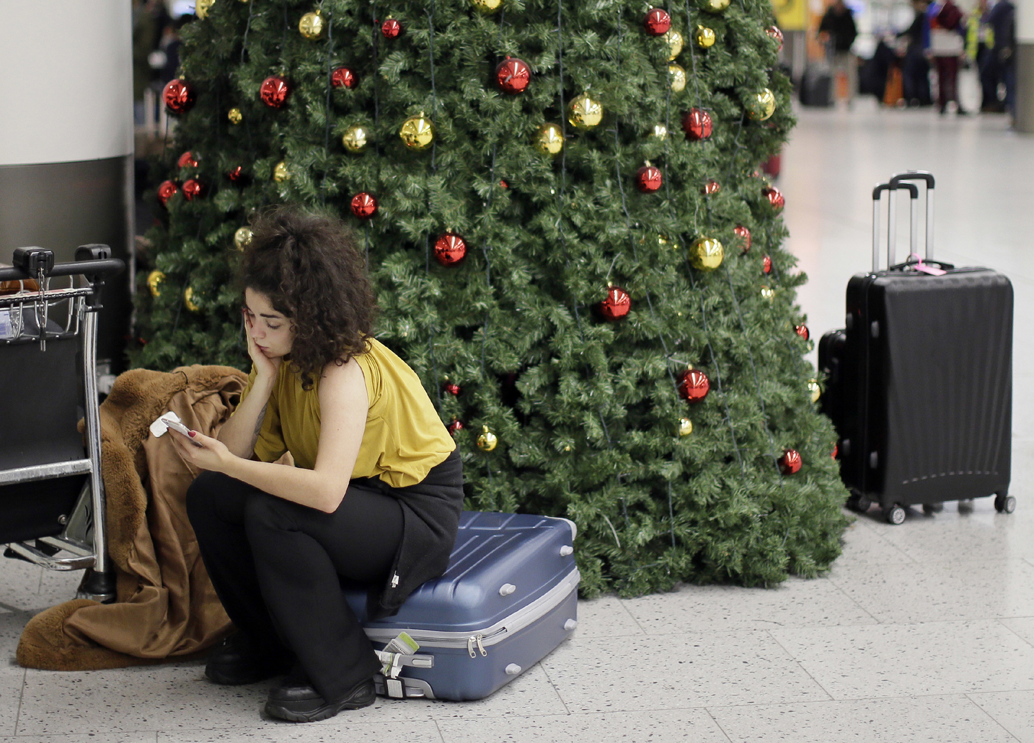 A woman waits in the departures area at Gatwick airport, near London, as the airport remains closed with incoming flights delayed or diverted to other airports, after drones were spotted over the airfield last night and this morning, Thursday, Dec. 20, 2018.[Photo: AP/Tim Ireland]