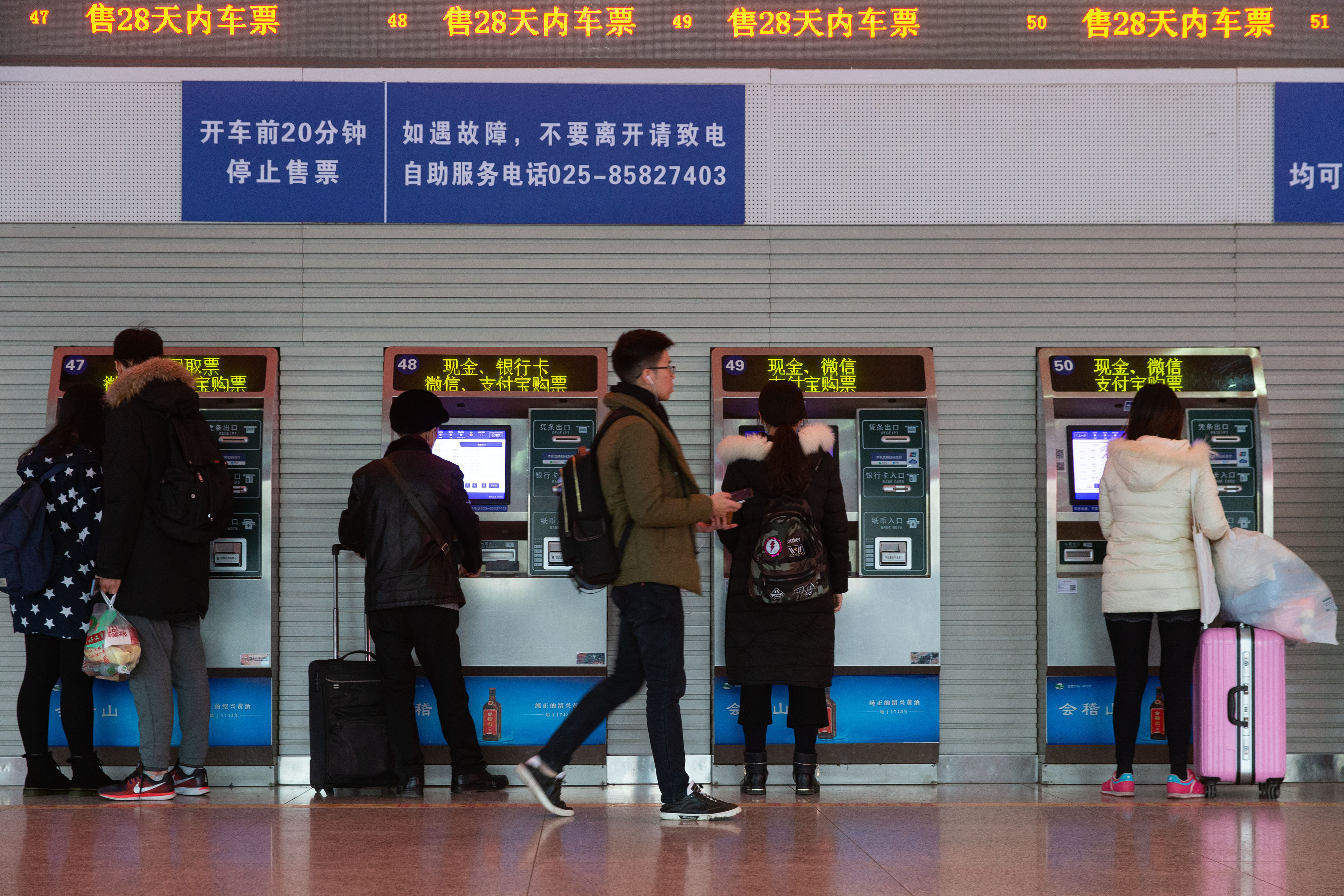 Passengers buy train tickets via ticket vending machines at a train station in Nanjing, Jiangsu Province on December 23, 2018. [File photo: IC]