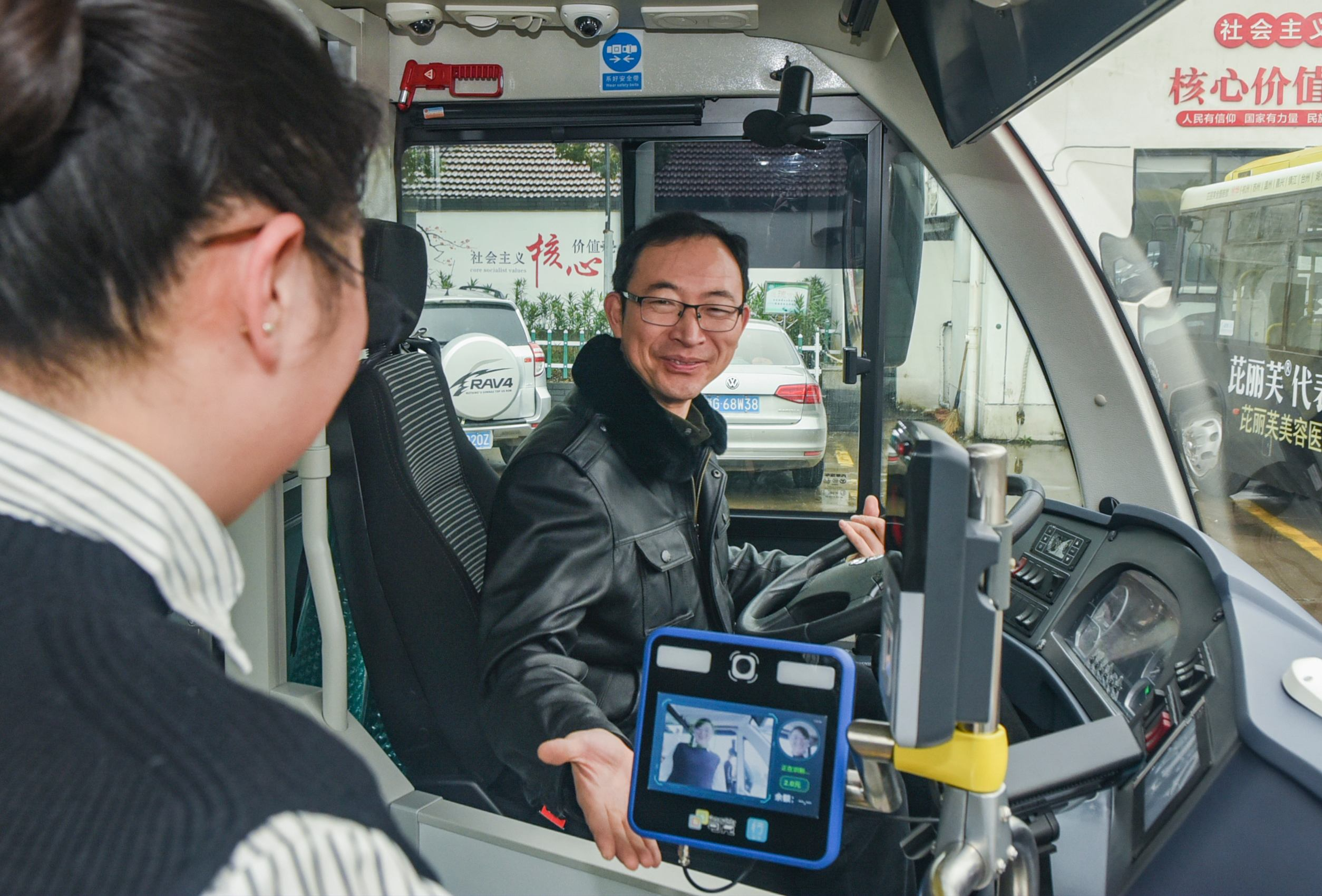 The bus diver looks as a passenger scans her face to pay her fare onboard a bus in Jinhua, Zhejiang Province, January 7, 2019. [Photo: IC]