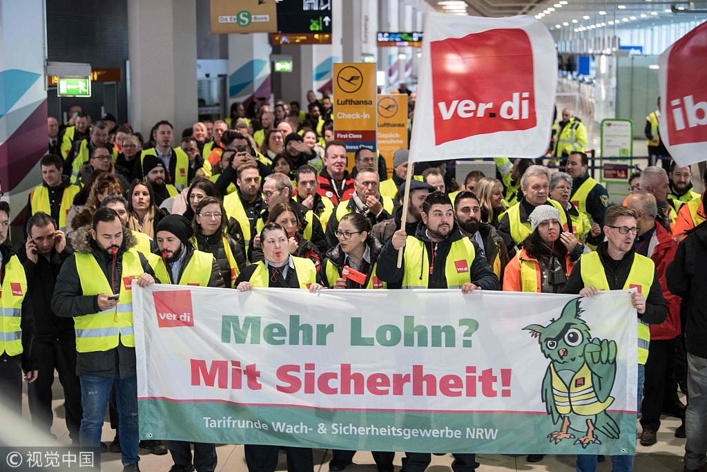 """Members of Germany's Verdi union hold a banner reading """"more pay? With security (certainty)"""" at a terminal during a one-day strike by security staff at Cologne's airport on January 10, 2019. [Photo: VCG]"""