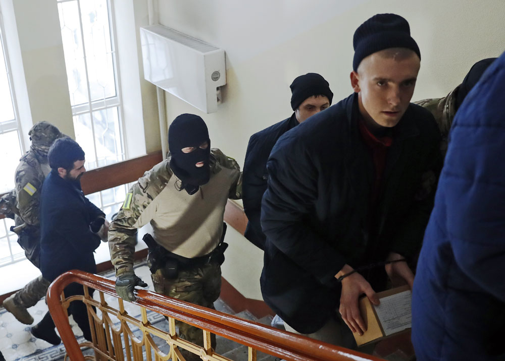 Ukrainian sailors are escorted by Russian intelligence agency officers to a court room in Moscow, Russia, Tuesday, Jan. 15, 2019. [Photo: AP/Pavel Golovkin]
