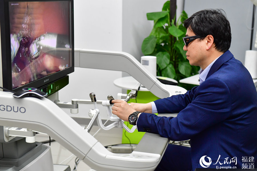 Doctor Liu Rong operates remotely during surgery on a pig using 5G technology in Fuzhou, Fujian Province. [Photo: people.cn]