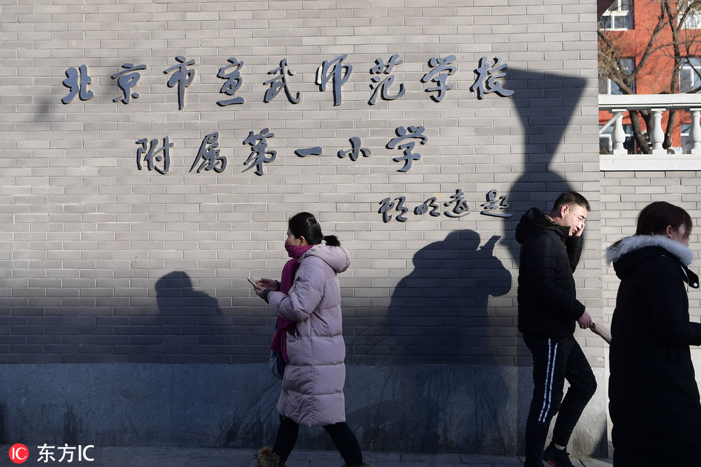 Pedestrians walk past Beijing No.1 Affiliated Elementary School of Xuanwu Normal School after a worker attacked a group of pupils with a hammer at the school in Beijing, January 8, 2019. [Photo: IC]