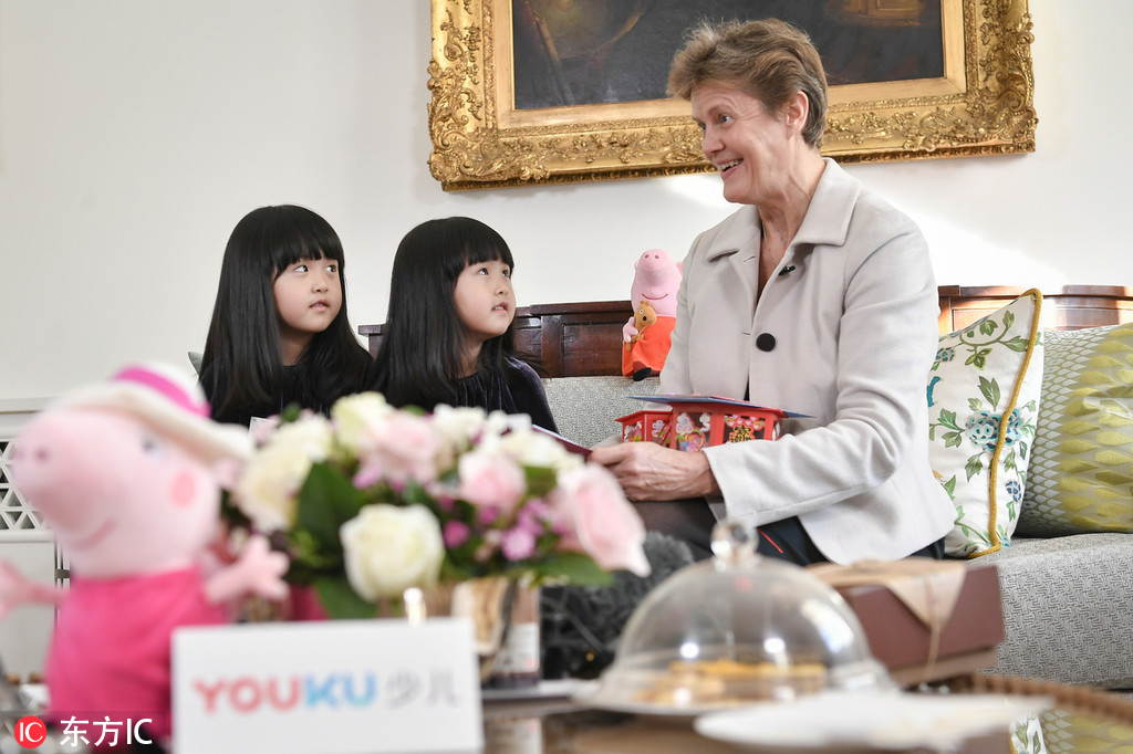 Britain's Ambassador to China Barbara Woodward receives gifts from Peppa Pig fans Mi Ai and Mi Ni during afternoon tea at the British Embassy in Beijing on Monday, January 21, 2019. The twins' mother had helped the girls to post a video on Weibo sharing their wish to visit Buckingham Palace. [Photo: IC]