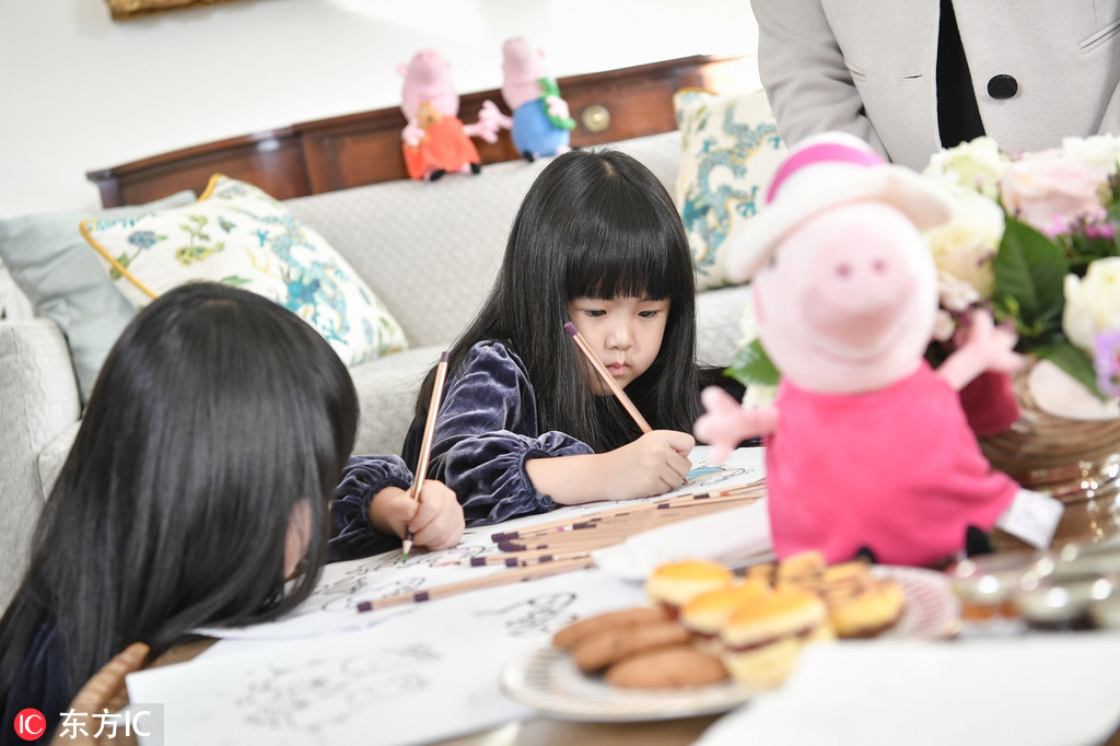 Peppa Pig fans Mi Ai and Mi Ni make paintings during afternoon tea with the British Ambassador to China Barbara Woodward at the British Embassy in Beijing on Monday, January 21, 2019. [Photo: IC]