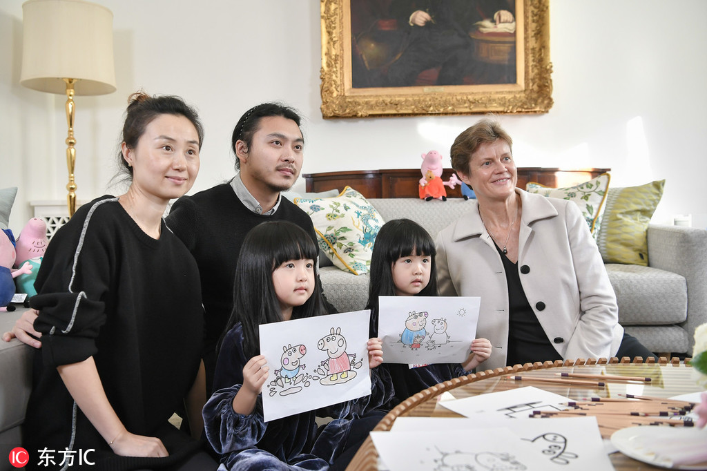 Peppa Pig fan Mi Ai and Mi pose with the British Ambassador to China Barbara Woodward and the Peppa Pig paintings they made during afternoon tea at the British Embassy in Beijing on Monday, January 21, 2019. [Photo: IC]