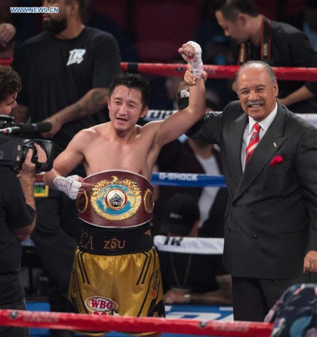 Zou Shiming (L) of China celebrates after defeating Prasitak Phaprom of Thailand in a WBO flyweight title boxing match in Las Vegas, the United States, Nov. 5, 2016. [Photo: Xinhua]