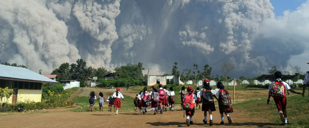School children walk as Mount Sinabung erupts in Karo, North Sumatra, Indonesia, Monday, Feb. 19, 2018. Rumbling Mount Sinabung on the Indonesian island of Sumatra has shot billowing columns of ash more than 5,000 meters (16,400 feet) into the atmosp