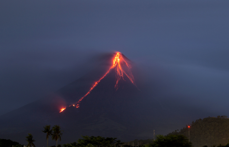 Lava continues to cascade down the slopes of Mayon volcano as seen from Legazpi city, Albay province, around 340 kilometers (210 miles) southeast of Manila, Philippines, at dawn Tuesday, Jan. 16, 2018. Glowing red lava was rolling down the slopes of a Philippine volcano as authorities maintain a warning of a possible hazardous eruption. (AP Photo/Earl Recamunda)