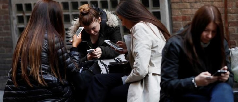 "Women look at their mobile phones in London, Britain October 6, 2016. REUTERS/Stefan Wermuth  SEARCH ""WERMUTH PHONES"" FOR THIS STORY. SEARCH ""THE WIDER IMAGE"" FOR ALL STORIES."