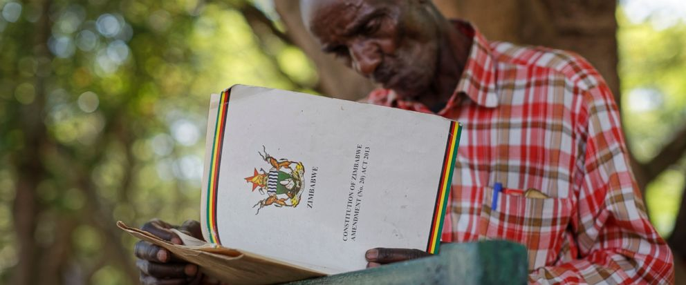An unemployed man reads up on Zimbabwean constitutional law to understand the process of possible presidential impeachment, in a park opposite the parliament building in downtown Harare, Zimbabwe Tuesday, Nov. 21, 2017. Zimbabwean President Robert Mu