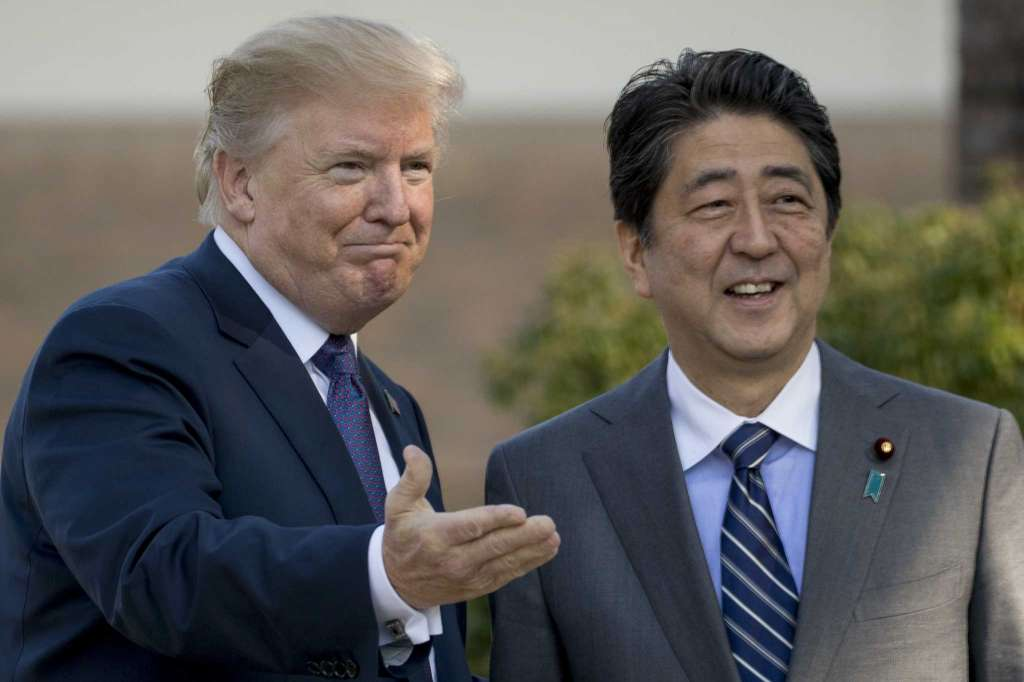 Image result for US President Donald Trump shakes hands with Japan's Prime Minister Shinzo Abe at Kasumigaseki Country Club in Kawagoe, north of Tokyo, November 5, 2017.