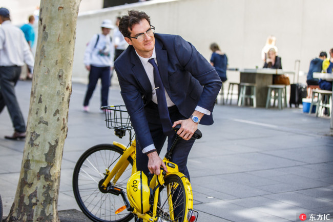 A man locks an ofo shared-bike after he finishes riding in Sydney, Australia, on September 25, 2017. [Photo: IC]