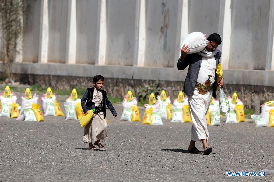 Yemeni state employees gather to receive food rations in Sanaa