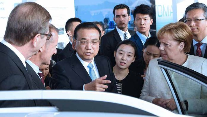 Chinese Premier Li and German Chancellor Merkel ride in a self-driving vehicle at cooperation exhibition