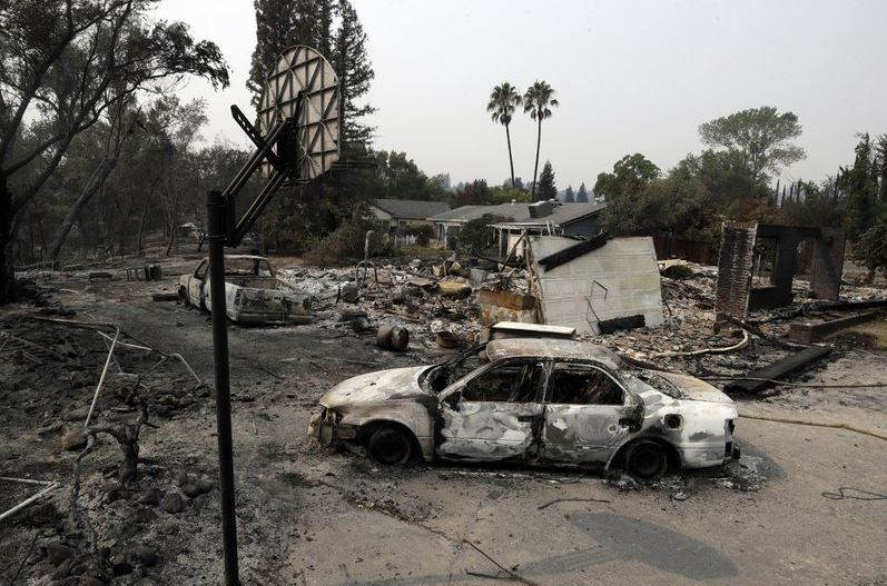 Thousands more flee wildfires as deadliest blaze slows down