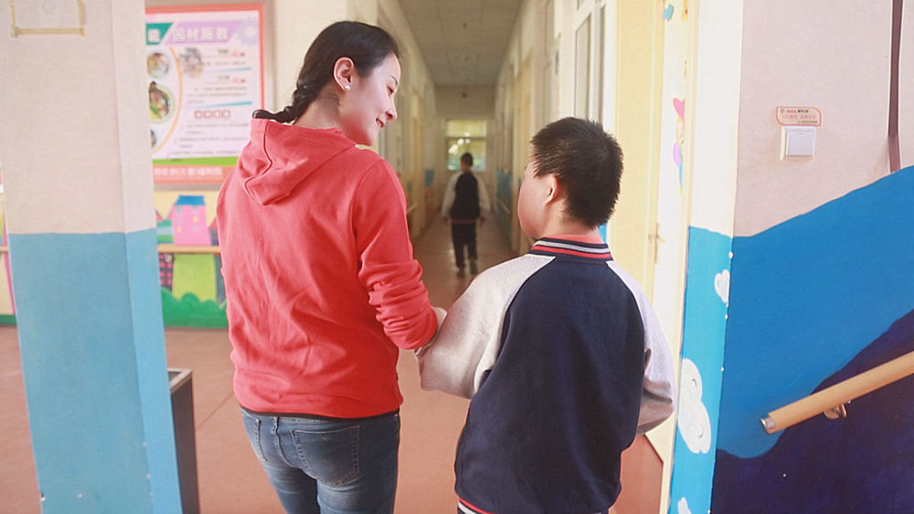 Young teachers play dual roles in helping China's handicapped orphans